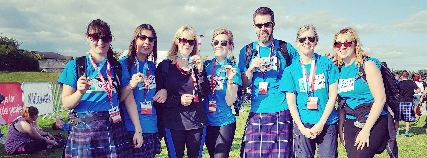 A group of men and women with their medals for finishing the Dundee Kiltwalk 2017