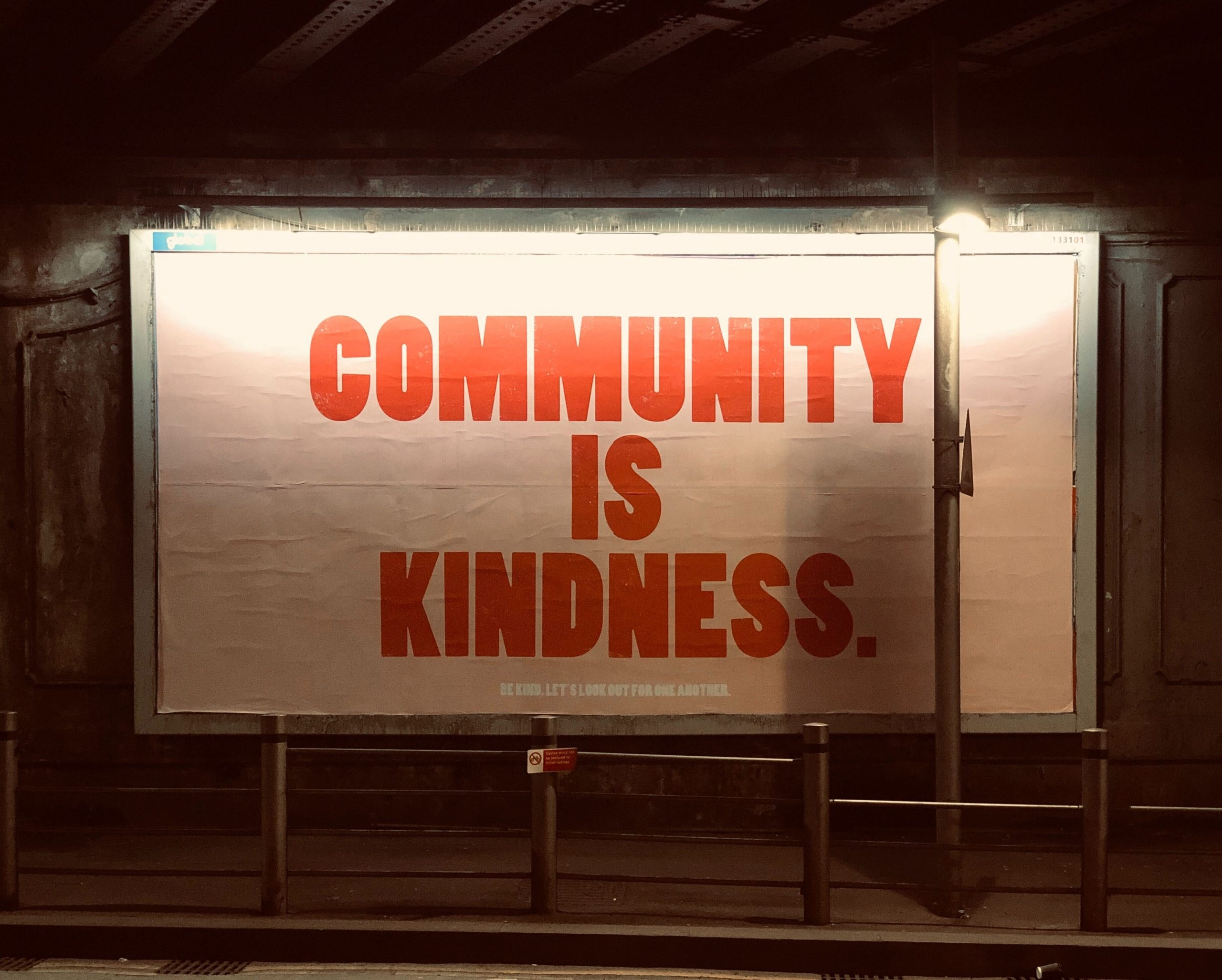 white billboard with community is kindness in red