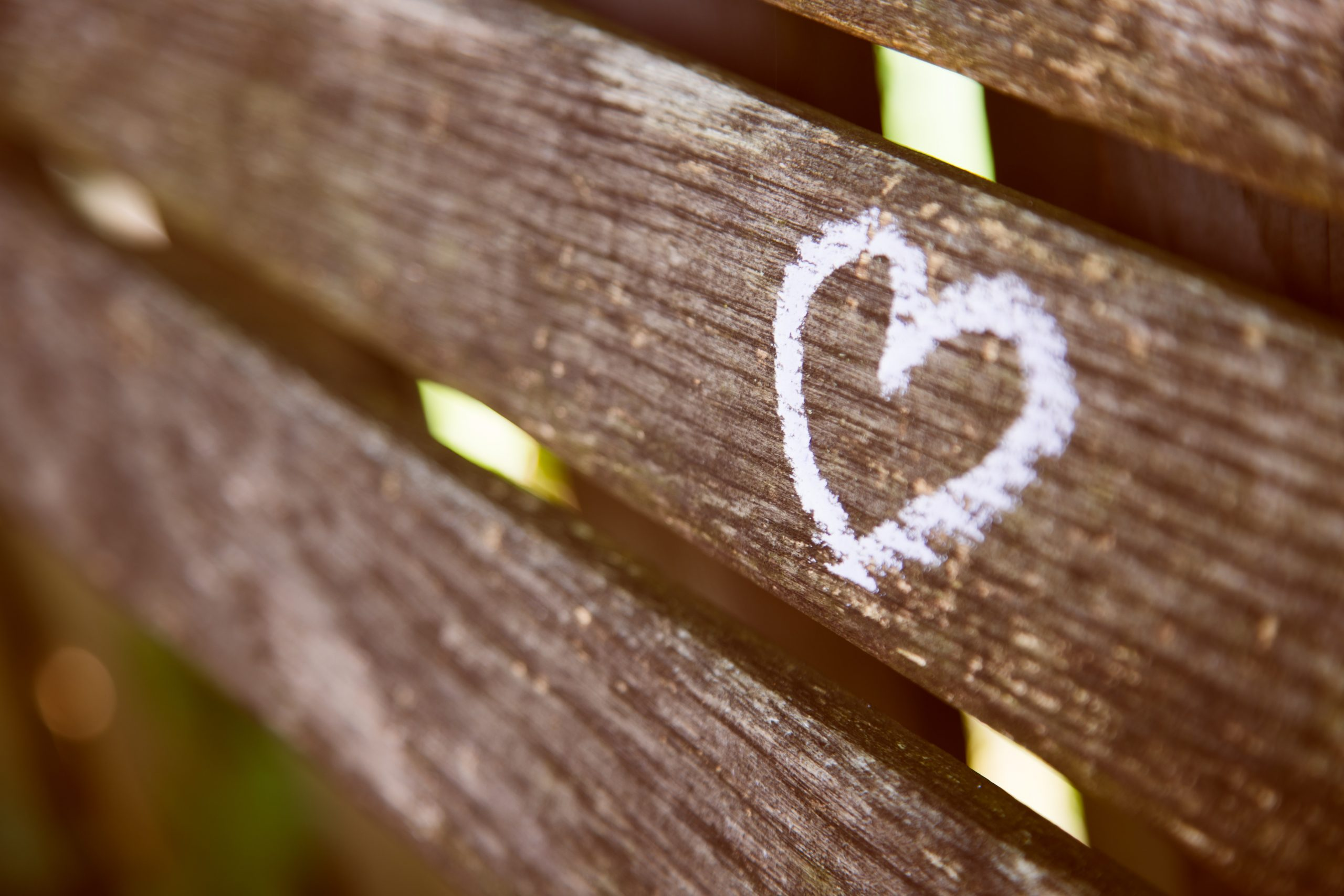 a heart drawn in white chalk on a bench