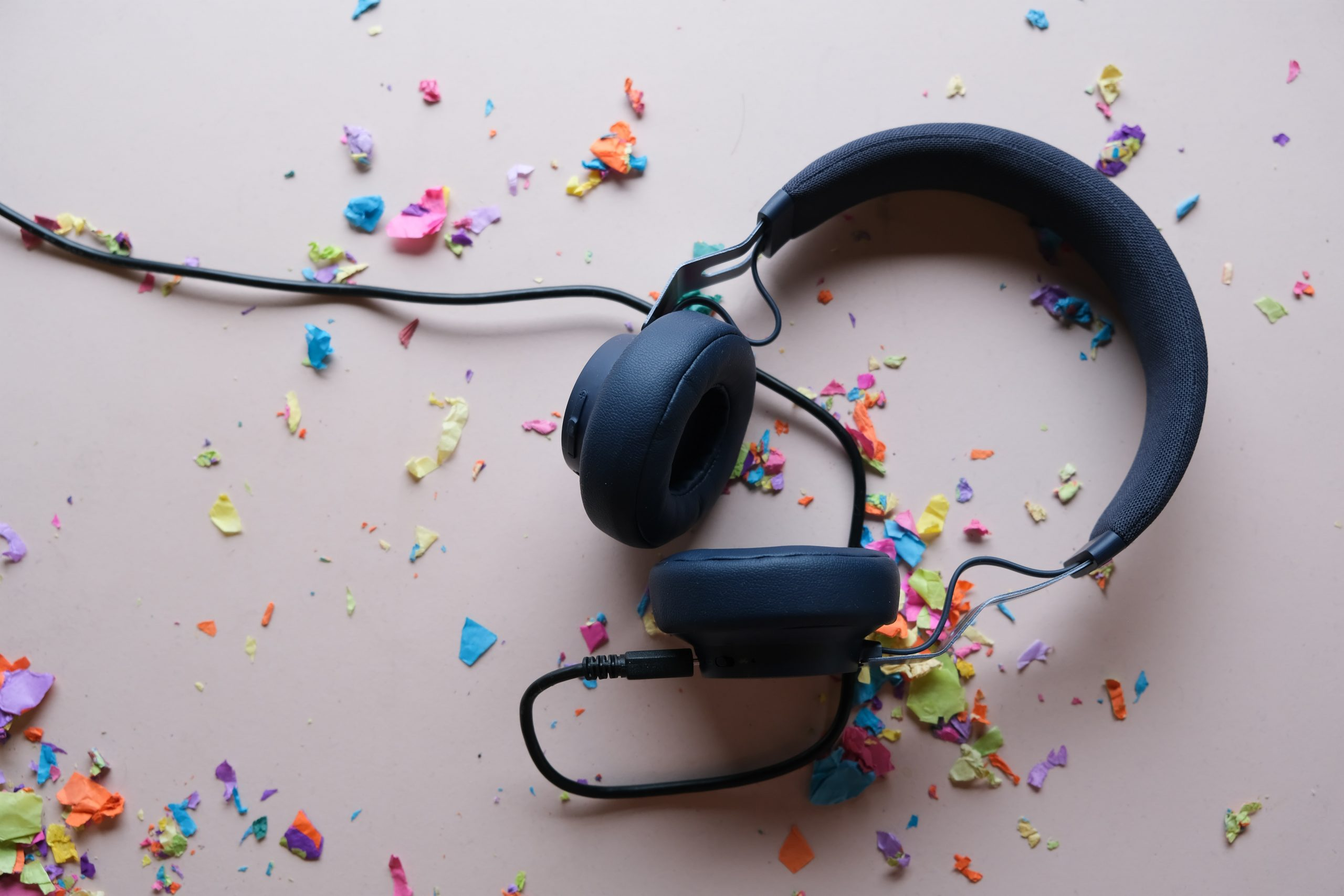 black headphones lying in scattered colourful confetti