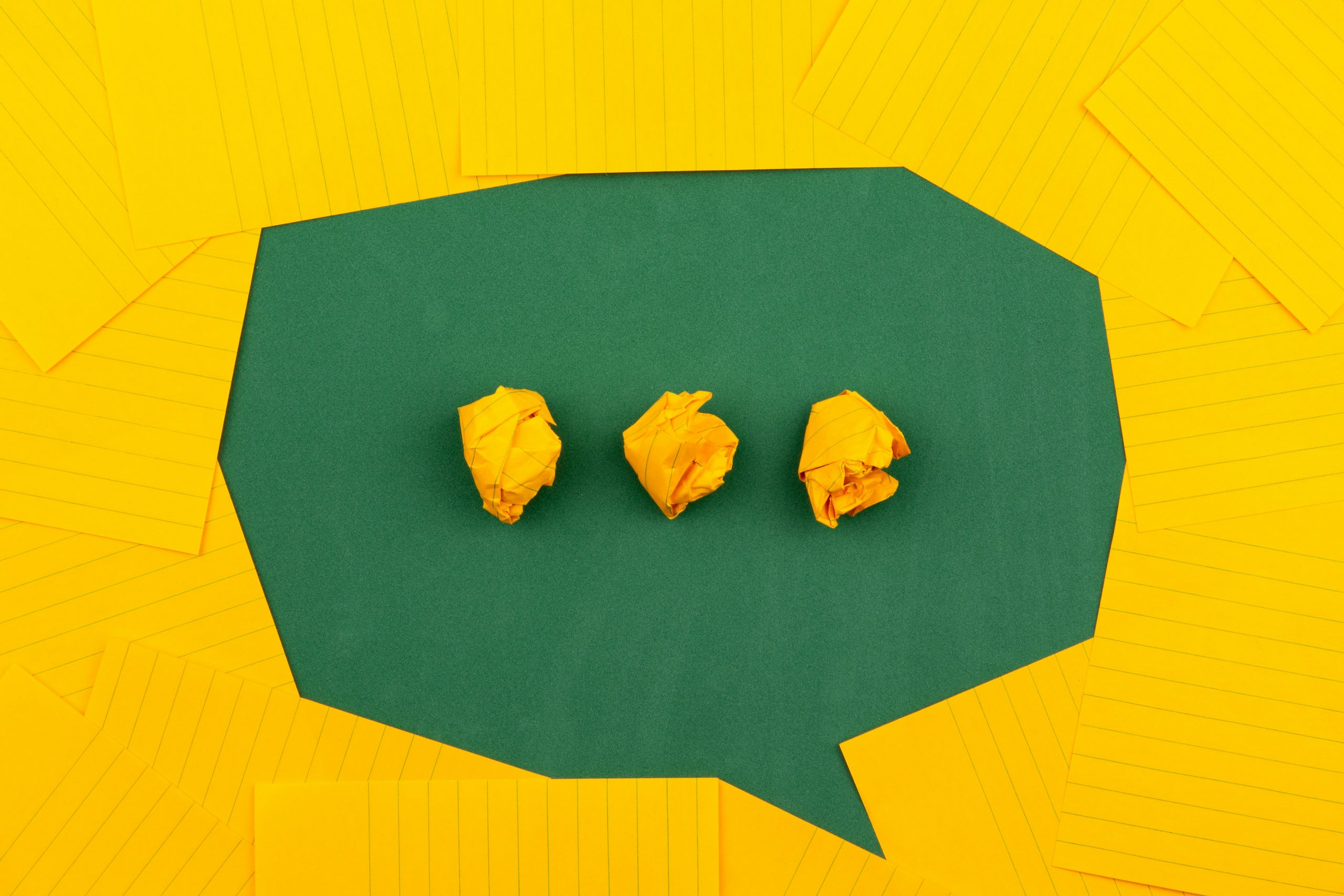 a green speech bubble made out of yellow paper